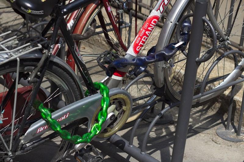 Un exemple illustrant la façon d'attacher correctement un vélo : une chaîne lie la roue avant et le cadre à un point fixe, tandis qu'une deuxième chaîne lie la roue arrière au cadre.