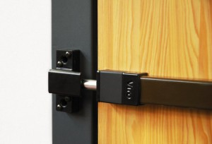Exemple de système de protection mécanique « Barre de sûreté Universale » appliquée sur une porte en bois.